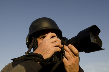 A male press photographer wears a protective helmet and vest and takes photos with a professional camera Stock Photo