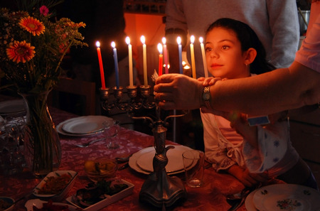chanukah: A family is lighting a candle for the Jewish holiday of Hanukkah. Stock Photo
