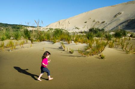 Little girl runs over Te Paki sand dunes in Northland New Zealand.