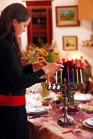 jewish home: A woman prays before lighting candles for the Jewish holiday of Hanukkah.