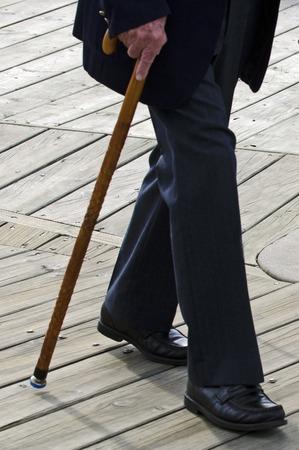 Perfil de la mitad inferior de un anciano o anciana persona que camina con un bastón de caña de madera que llevaba un traje oscuro. Foto de archivo