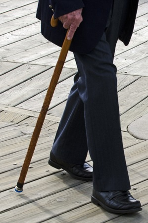 Profile of bottom half of an old man or elderly person walking with a wood cane stick wearing a dark suit.