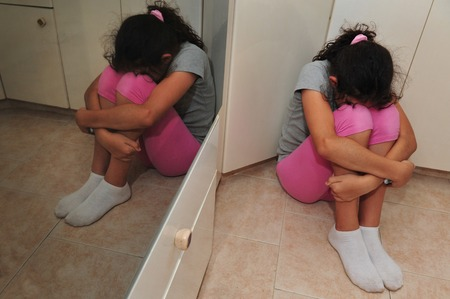 cries: a young girl hides her face and cries on the corner of a kitchen Stock Photo