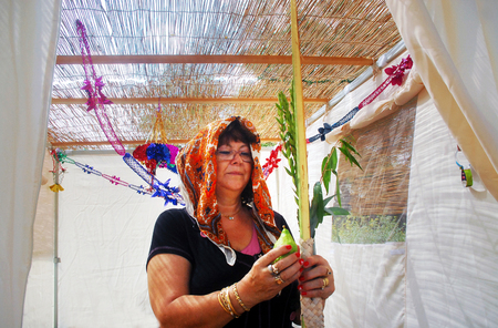 succos: A Jewish woman bless on the four species in the Sukkah in Sukkoth jewish holiday.