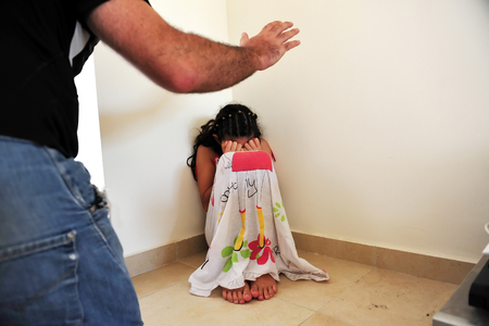 smack: A young girl who is a victim of domestic violence tries to hide in a corner from being punished by a male