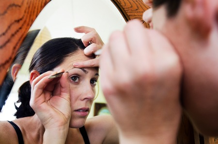 fair complexion: Young caucasian woman looks in the mirror and plucks hair from her eyebrow.