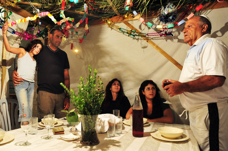 succos: Israeli Jewish family celebrating the Jewish holiday of Sukkoth.