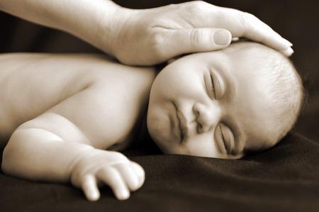 Woman hand on newborn baby sleep in peace.