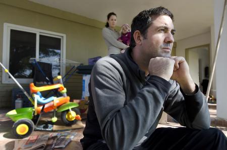 젊은 부모와 그들의 딸들이 집 밖에서 골 판지 상자 옆에 서있다. 이혼, 노숙자, 퇴거, 실업, 금융, 결혼 가족 문제를 설명하는 개념 사진.
