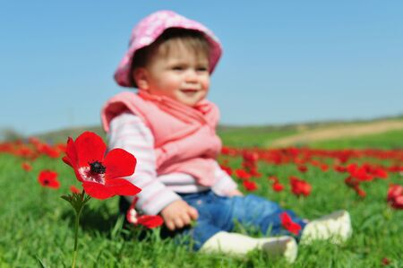 red poppies on green field: An image of a baby girl sitting in a green field with red poppies