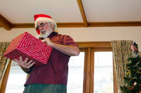 christmas savings: Senior man dressed up as Santa claus in front of noel tree is giving presents on Xmas day. Stock Photo