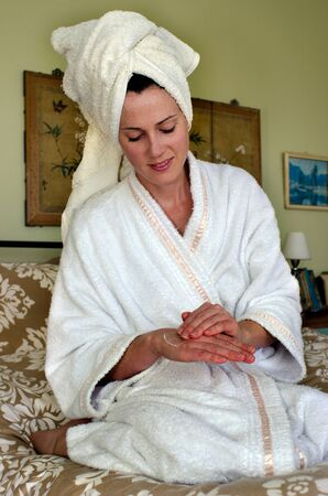 A young caucasian woman in a dressing gown sits on a bed and applies moisturiser to her skin.