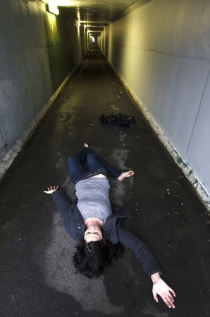 murder scene: Crime scene concept photo of a murder victim woman lying dead on the ground of a tunnel.