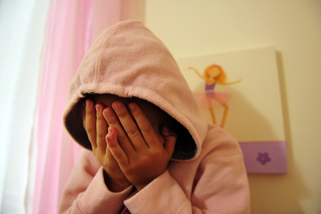 cries: A young girl who is a victim of domestic violence cries on her bed in her bedroom Stock Photo