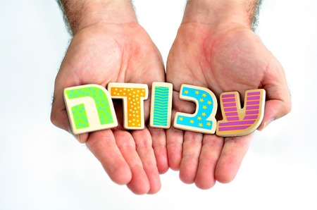 job hunting: Man hands hold the word WORK in Hebrew text (Avoda) isolated on white background multi purpose concept of Job hunting, unemployment, employment, work seeking, seeking employment, work search in Israel. Stock Photo