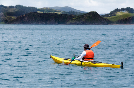 kayaker: Man rows a yellow sea kayak in the bay of Island New Zealand. Very popular travel destination of NZ