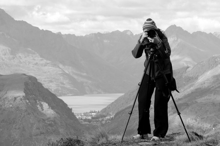 documenting: Professional on location and nature photographer (woman) photographing landscape  outdoor. (BW) Stock Photo