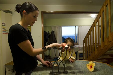 jewish home: Young Jewish mother and her daughter lights and bless on the shabbat Candles with  before shabbat