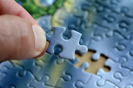 final piece of puzzle: Hand holds the last puzzle piece.Business concept for completing the final puzzle piece