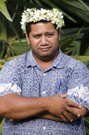 cook out: Portrait of Polynesian Pacific Island Tahitian mature male wearing exotic flowers top bouquet smile out side his home garden in Aitutaki lagoon Cook Islands.