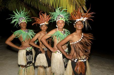 tahitian: Portrait of Polynesian Pacific Island Tahitian male dancers in colorful costume dancing on tropical beach. Stock Photo