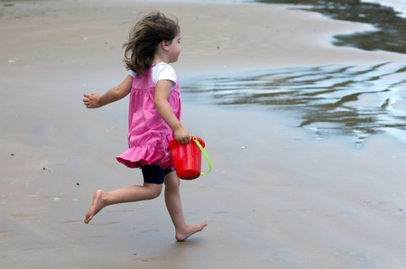 little girl smiling: Child girl runs on sandy beach during summer holiday.