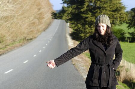 hitchhiking: Young woman hitchhiking in rural countryside area during autumn season.