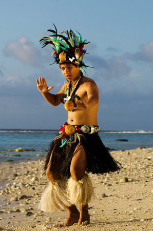 islanders: Portrait of attractive young Polynesian Pacific Island Tahitian male dancer in colorful costume dancing on tropical beach during sunset. Stock Photo