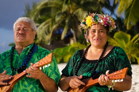 tahitian: Portrait of two mature Polynesian Pacific islanders couple sing and plays Tahitian Music with Ukulele guitars on tropical beach with palm trees in the background.