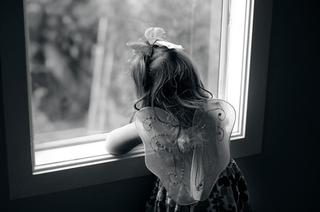 Sad little girl wearing angel fairy wings look outside from a home window.