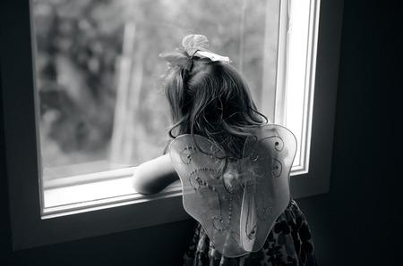 fairy tale princess: Sad little girl wearing angel fairy wings look outside from a home window.