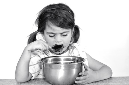 dispersed: Little girl eats chocolate cream. Concept photo of Child , children,depression,dispersed, food, health care , diet, eating disorder,bulimia. (BW) copy space Stock Photo