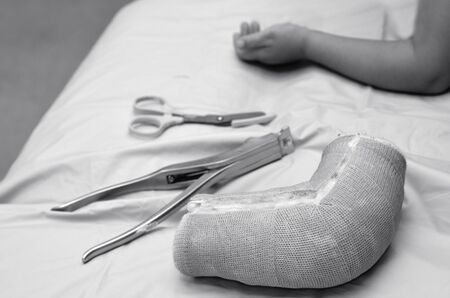 home health care: Removed child arm cast on hospital bed with child recovered arm in the background. Concept photo of children, health care,outdoor accidents, game accidents, playground accidents, home accidents.(BW)