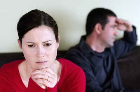 people arguing: Portrait of unhappy young couple who have fallen out over a disagreement sitting on a sofa. Woman in the front and the man in the background. Stock Photo