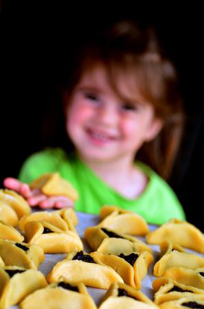 haman: Jewish child (girl age 3) eats Hamentashen, Ozen Haman, cookies on Purim Jewish holiday.