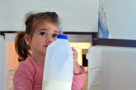 no food: Hungry poor little girl holds a bottle of milk at home.