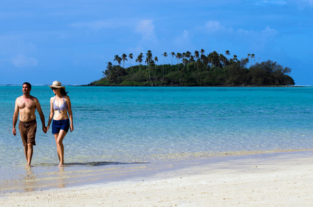 rarotonga: Attractive young happy couple on vacation hold hands and walks on Muri beach lagoon in Rarotonga, Cook Islands.