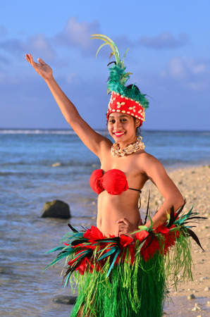tahitian: Portrait of Polynesian Pacific Island Tahitian female dancer in colorful costume dancing on tropical beach. Photo have MR Editorial
