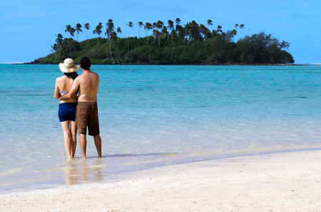 rarotonga: Attractive young happy couple on vacation hugs on Muri beach lagoon in Rarotonga, Cook Islands. Stock Photo