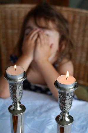 ユダヤ人の少女は、安息日イブのディナーの前に安息日ろうそくを照明に祝福を言います。 写真素材