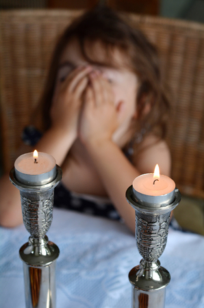 jewish home: Jewish girl says the blessing upon lighting the sabbath candles before shabbat eve dinner. Stock Photo