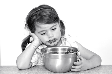dispersed: Little girl finished to eat big bowl of chocolate cream. Concept photo of Child , children,depression,dispersed, food, health care , diet, eating disorder,bulimia. (BW) copy space