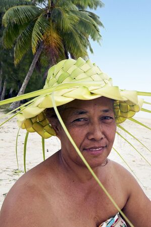 tahitian: Portrait of Polynesian Pacific Island Tahitian mature female wearing here handcraft of a hat knees out of palm leaveson tropical beach in Aitutaki lagoon Cook Islands.