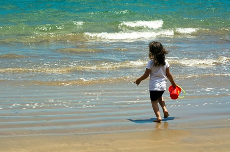 4 year old: Child (girl) runs into the sea with a bucket during summer holiday.