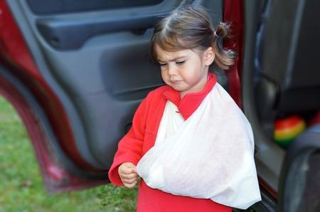 brazo roto: Sad little girl with a broken arm arrive at home. Foto de archivo