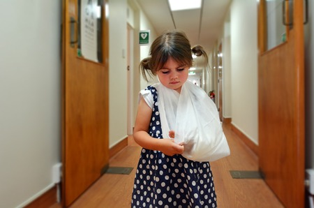 human arm: Sad little girl with a broken arm in hospital corridor. Stock Photo