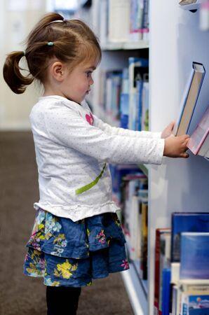 preescolar: preescolar de la muchacha que selecciona el libro en la biblioteca.
