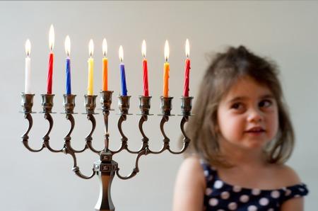 hanukka: Cute Jewish girl look at fully lit Hanukkah menorah during the Jewish holiday of Hanukkah.