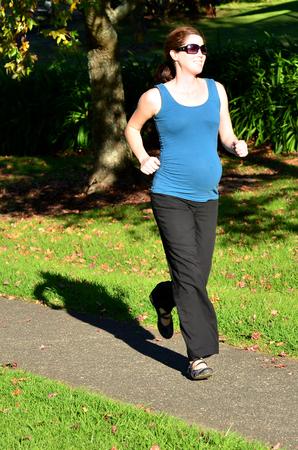 personas corriendo: Mujer embarazada ejecutar el ejercicio durante el embarazo al aire libre en el parque. Foto del concepto de la mujer el estilo de vida saludable y el cuidado de la salud. copyspace