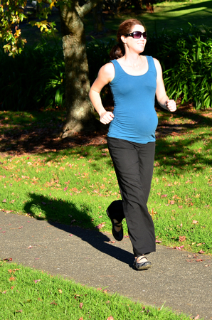 expectation: Pregnant woman run exercise during pregnancy outdoor at the park. Concept photo of women healthy life style and health care. copyspace Stock Photo